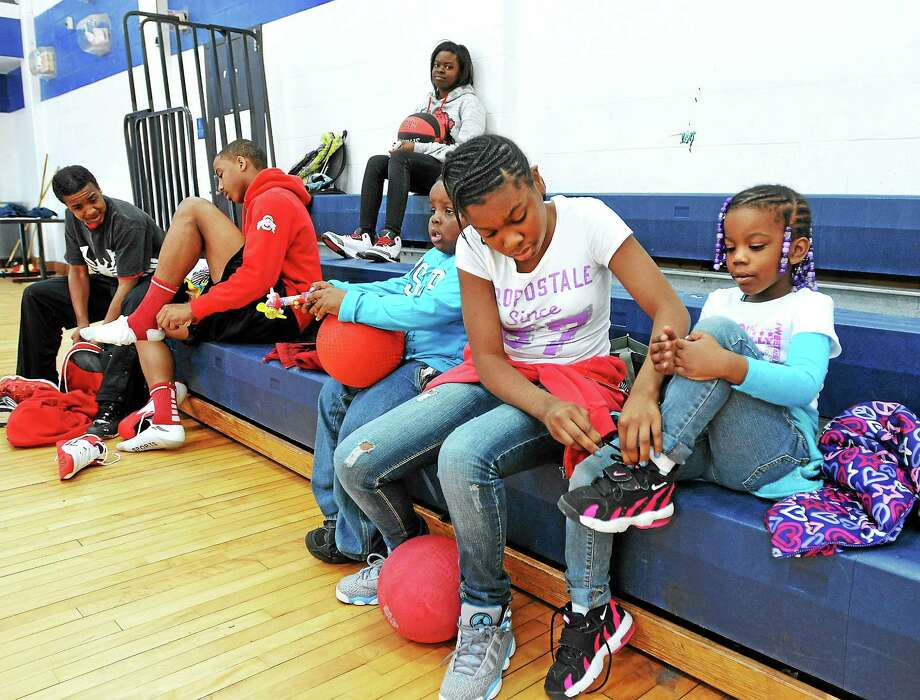 Aleah Doctor, 12, helps Deonna Bulls, 5, with her shoes as children enjoy free play time during spring vacation activities at James Hillhouse High School earlier this week in New Haven. Photo: Peter Casolino — New Haven Register