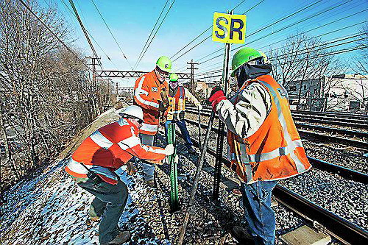 Metropolitan Transportation Authority workers install safety signals on its railroad lines.