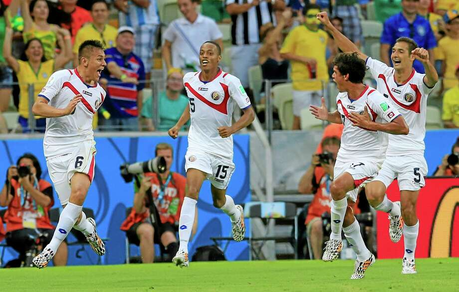 Costa Rica's Oscar Duarte, left, celebrates after scoring his side's second goal during a group D World Cup match against Uruguay on Saturday at the Arena Castelao in Fortaleza, Brazil. Photo: Bernat Armangue — The Associated Press   / AP