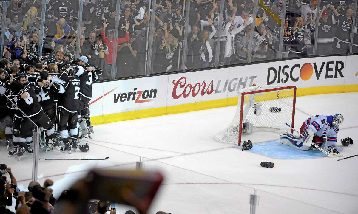 Kings players celebrate after their double-overtime win in Game 5 of the Stanley Cup finals as New York Rangers goalie Henrik Lundqvist drops to his knees on Friday in Los Angeles.