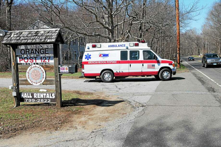 An ambulance leaves 630 Grassy Hill Road in Orange near Lake Wepawaug where the body of an unidentified man was discovered Saturday afternoon floating facedown. Photo: Peter Hvizdak — New Haven Register   / ©Peter Hvizdak /  New Haven Register