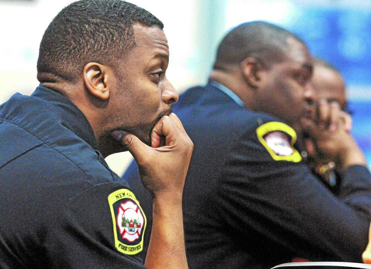 Firefighters listen as New Haven Fire Chief Allyn Wright speaks during the Greater New Haven NAACP meeting at St. Luke's Church Thursday.