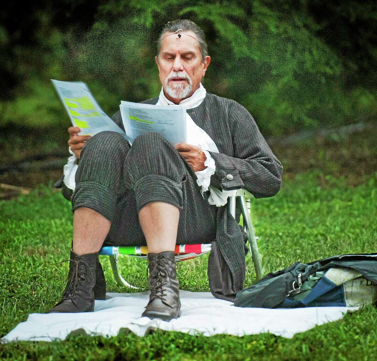 """Melanie Stengel — New Haven Register Actor Tracy Griswold goes over the script for """"Pericles"""" as he waits to go on stage in Edgerton Park Wednesday."""