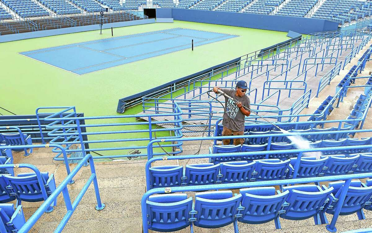 (Arnold Gold-New Haven Register) Edgar Miller, owner of Miller Construction Services, pressures washes the stands at Stadium Court at the Connecticut Tennis Center on 8/4/2014.