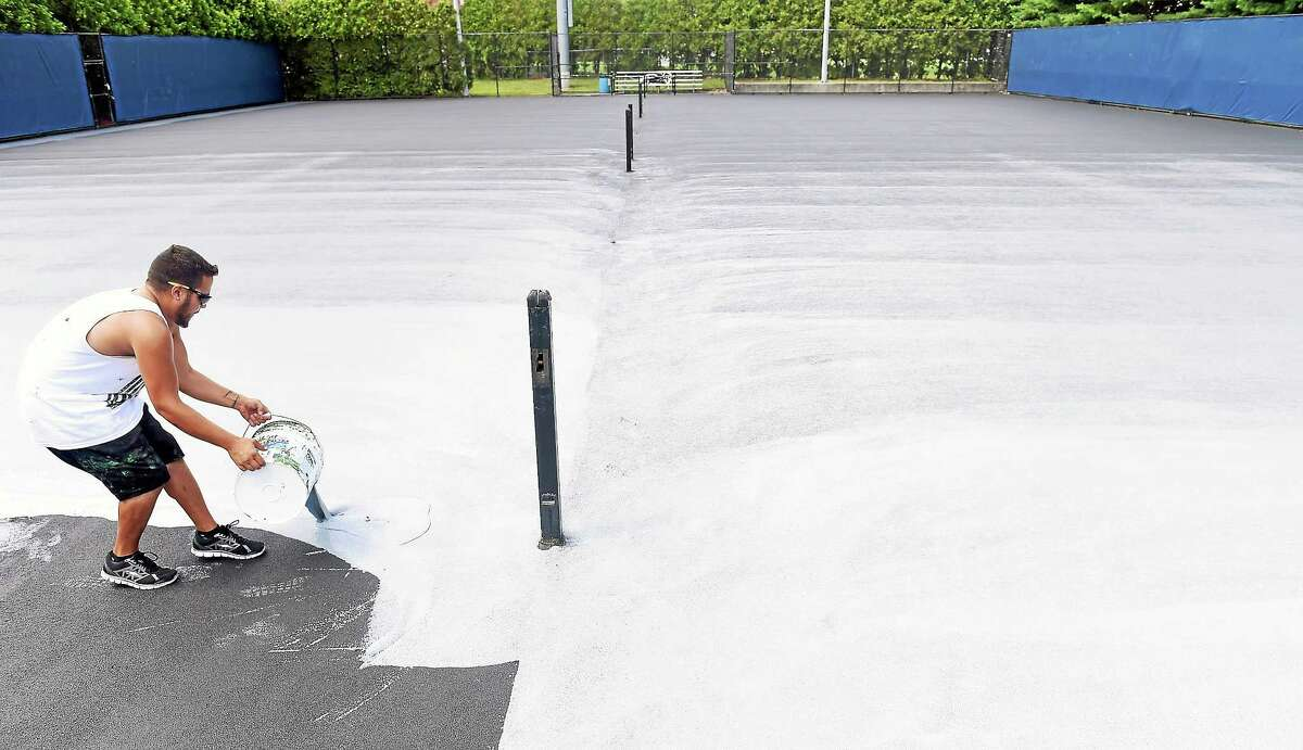 (Arnold Gold-New Haven Register) Janiel Crespo of Hartford pours a latex/rubber cushioning material to be spread out on a practice court at the Connecticut Tennis Center on 8/4/2014.