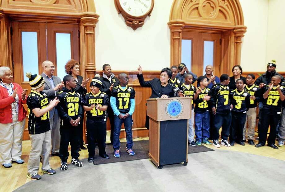 (Photo by Peter Hvizdak - New Haven Register)  New Haven Mayor Toni Harp with the New Haven Steelers New Haven Pop Warner Steelers Pee Wee team of 9-12 year olds at City Hall Thursday, December 4, 2014 during press conference and check presentation giving $10,000 to the team for traveling expenses. The team is  2014 Connecticut and regional Pop Warner Youth Football champions  who will compete in a  national championship tournament Saturday  in Florida. Photo: ©2014 Peter Hvizdak / ©2014 Peter Hvizdak