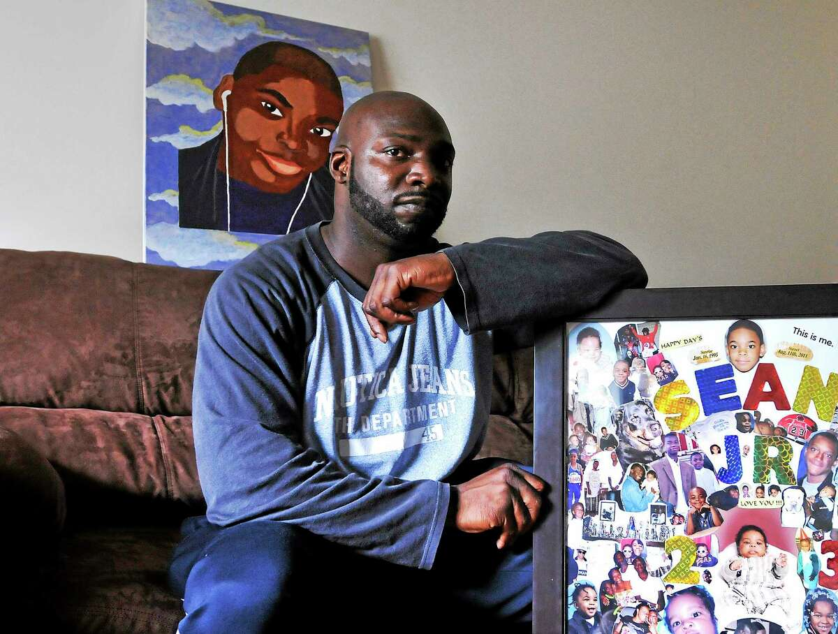 (Peter Casolino-New Haven Register) Sean Reeves Sr. lost his son Sean Jr. in 2011 to a shooting in New Haven. He reflects on Father's Day since his son's death. He is shown in his East Haven home with a collage, right, and a painting of his son done by a family member, behind him. June 10, 2014. pcasolino@newhavenregister.com