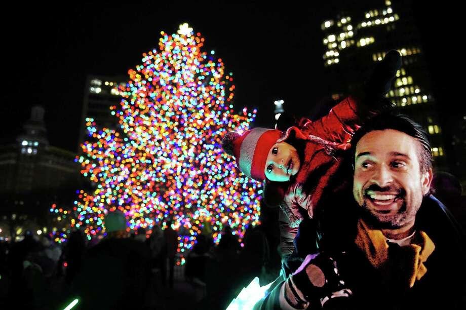 Christopher Cavallaro and his son Sebastian, 2, of Hamden, enjoy the festivities during Thursday's Christmas tree lighting on the New Haven Green. Photo: Peter Hvizdak — New Haven Register    / ©2014 Peter Hvizdak