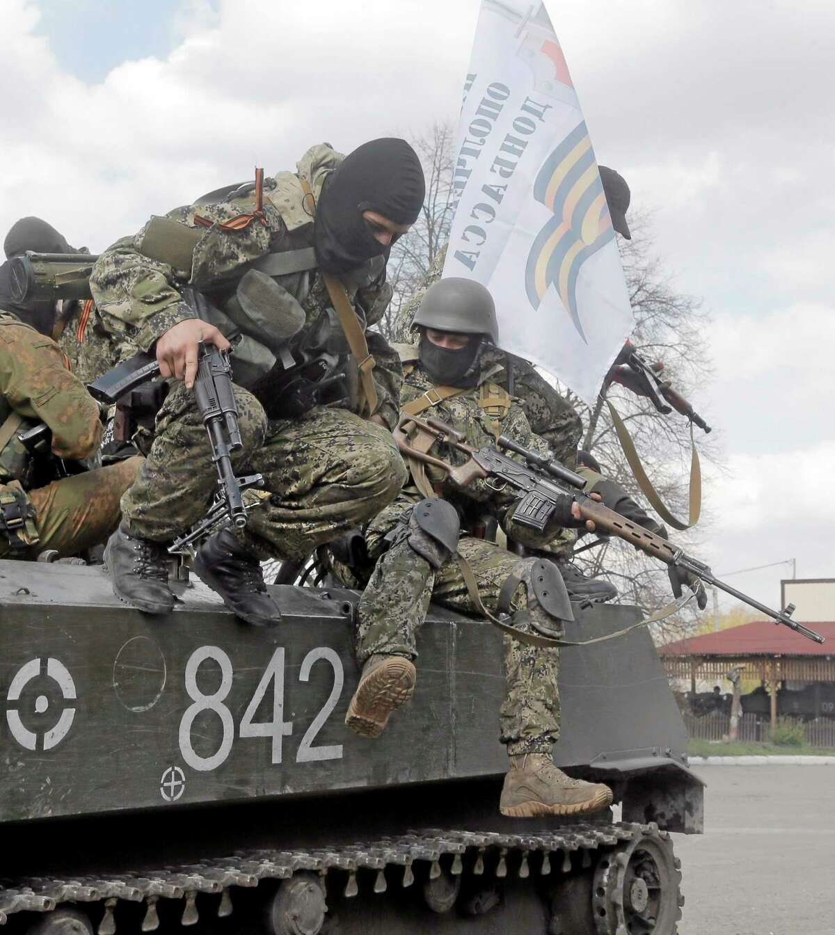 Pro-Russian gunman jump from a combat vehicle in downtown Slovyansk on Wednesday, April 16, 2014. The troops on those vehicles wore green camouflage uniforms, had automatic weapons and grenade launchers and at least one had the St. George ribbon attached to his uniform, which has become a symbol of the pro-Russian insurgency in eastern Ukraine. (AP Photo/Efrem Lukatsky)