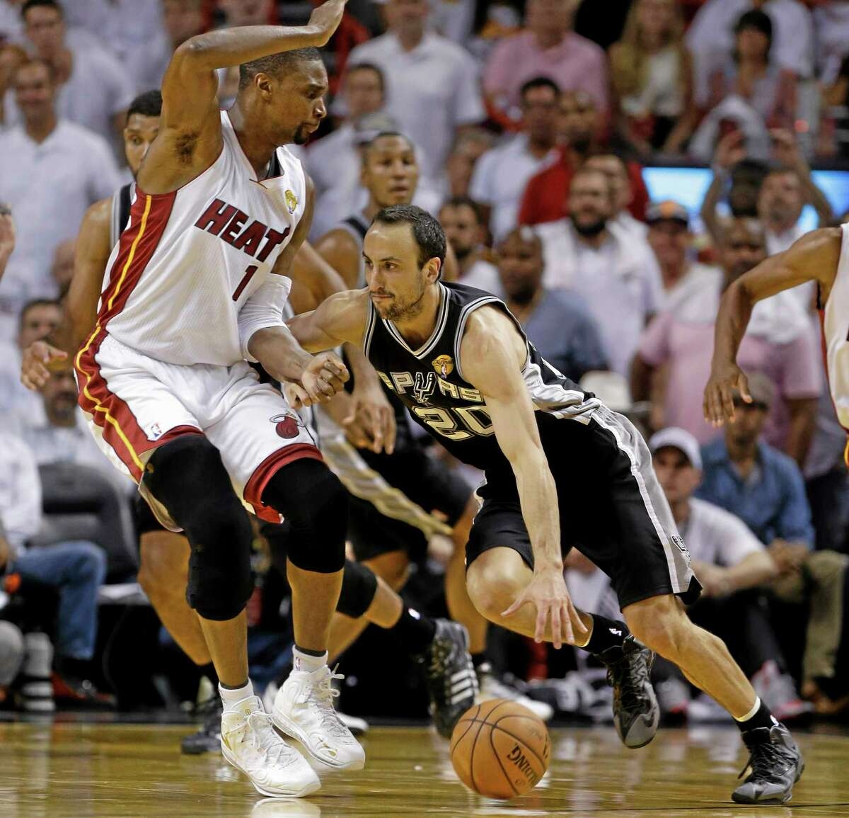 San Antonio Spurs guard Manu Ginobili (20) dribbles past Miami Heat center Chris Bosh (1) during the second half in Game 4 of the NBA Finals.