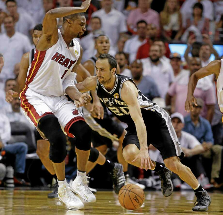 San Antonio Spurs guard Manu Ginobili (20) dribbles past Miami Heat center Chris Bosh (1) during the second half in Game 4 of the NBA Finals. Photo: Lynne Sladky — The Associated Press   / AP