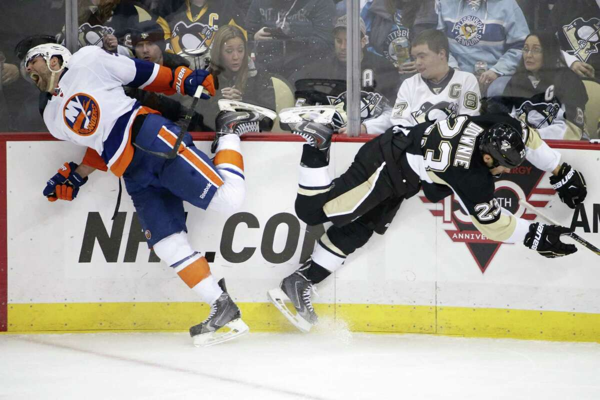 The Penguins' Steve Downie collides with the New York Islanders' Johnny Boychuk, left, along the boards during the third period of a Nov. 21 game in Pittsburgh.