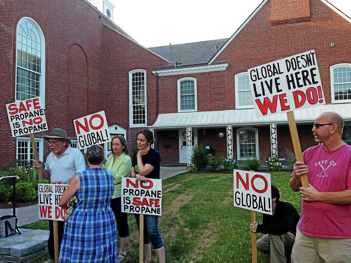 Opponents of the propane proposal carry signs outside Andrews Memorial Town Hall Monday.