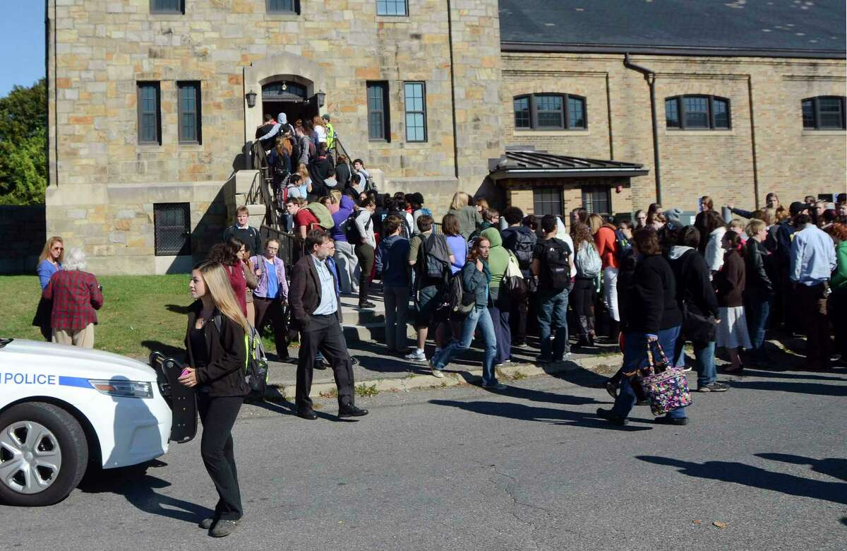 In this Monday, Oct. 6, 2014 photo, Massachusetts College of Liberal Arts students, faculty and staff are evacuated into the armory in North Adams, Mass., following a bomb threat on campus.