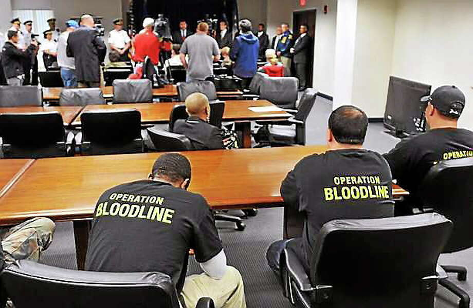 "DEA agents wear special shirts with ""Operation Bloodline"" at a press conference in May 2012 announcing that 105 individuals have been charged with New Haven-area narcotic trafficking and firearm offenses. Photo: Peter Casolino — New Haven Register — File Photo"