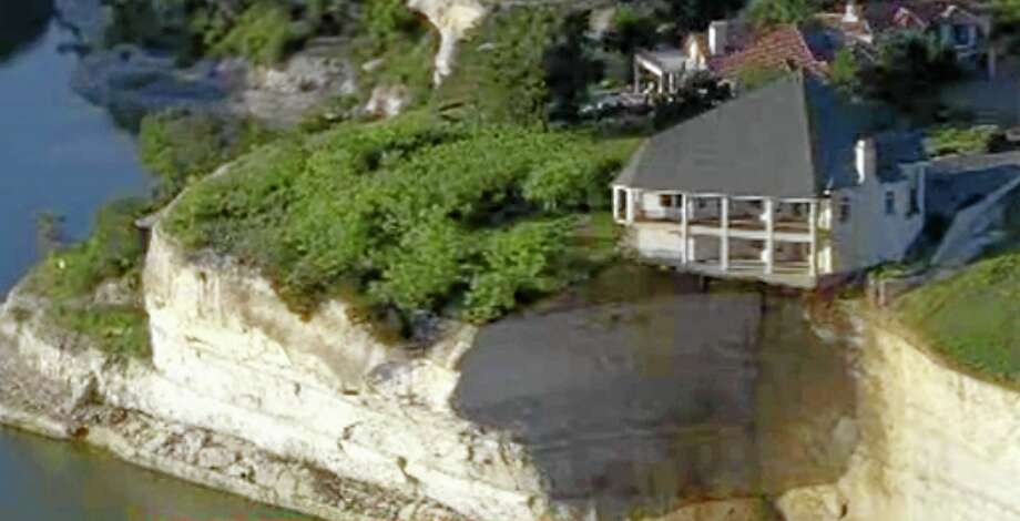 In this image taken from Tuesday, June 10, 2014 video provided by WFAA-TV, a luxury house teeters on a cliff about 75 feet above Lake Whitney in Whitney, Texas. WFAA-TV reported Wednesday, June 11, 2014 that the house has been condemned and the owners evacuated about two weeks ago. (AP Photo/WFAA.com) Photo: AP / WFAA.com