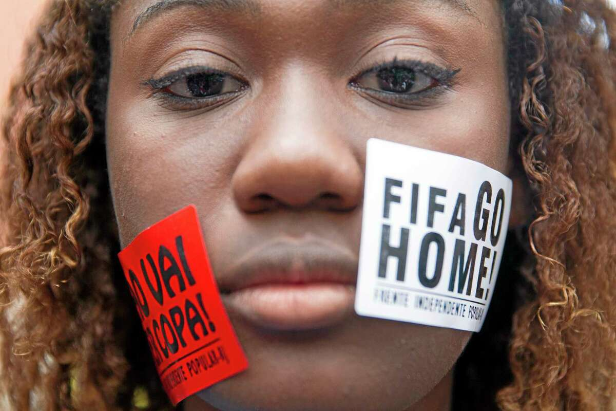 """A woman protests with signs pasted on her face that read """"FIFA Go Home"""" and """"Will not have a Cup"""" during a march against the World Cup 2014 at the Copacabana beach, in Rio de Janeiro, Brazil, Thursday, June 12, 2014. Protesters are demanding better public services and protesting the money spent on the soccer tournament. (AP Photo/Leonardo Wen)"""