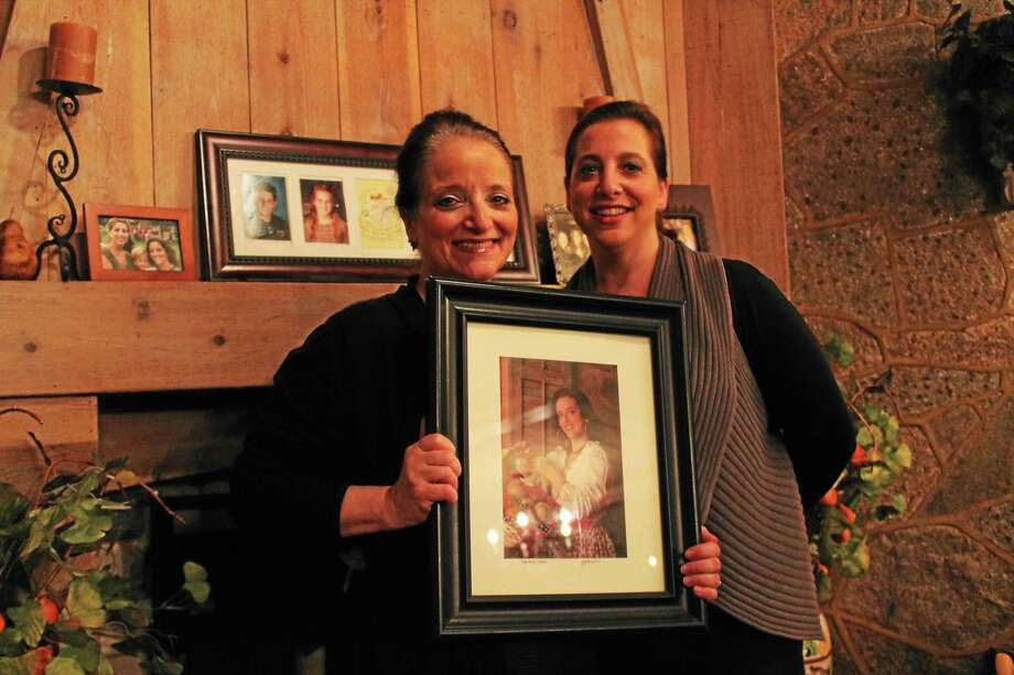 Antonio's restaurant owner Gena Colavolpe, left, and daughter Andrea Finta, right, say the time is right to move on. In Colavolpe's hands is a portrait of her other daughter, Gina, the restaurant's master chef. Photo: Evan Lips — New Haven Register