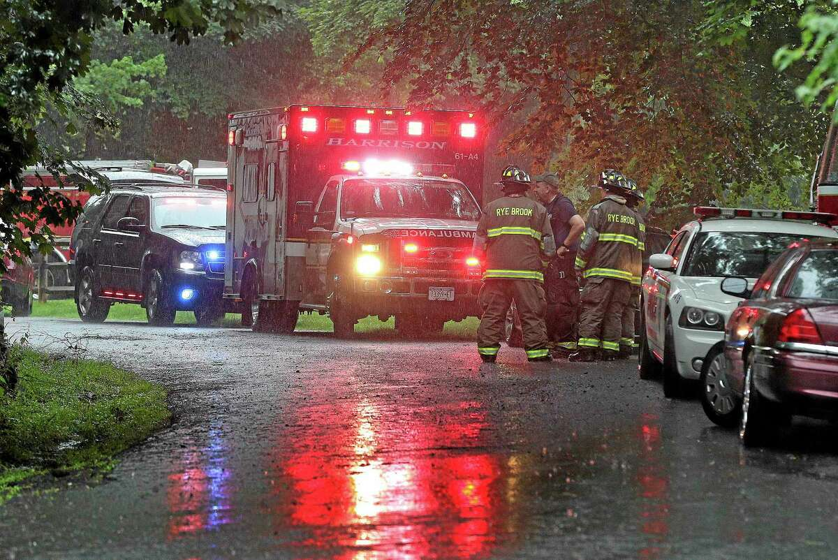 Emergency vehicles and personnel stand near a command post set up for a small plane that crashed on a road just west of Westchester County Airport, Friday, June 13, 2014, in Purchase, N.Y. The single-engine plane took off just after 8 a.m. and went down after hitting some trees, killing Richard Rockefeller, a great grandson of Standard Oil co-founder John D. Rockefeller.
