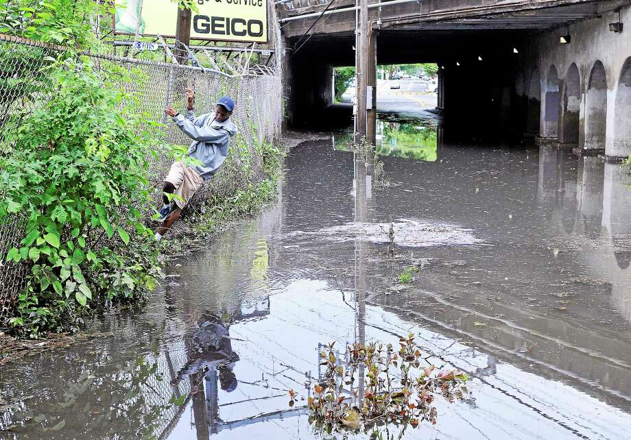 """James Hilton Jr. finds a unique route around the deep floodwaters along Humphrey Street in New Haven after the torrential downpour Friday afternoon. Hilton had to get to work, and said """"there was no other way.""""  (Peter Casolino — New Haven Register) Photo: Journal Register Co."""