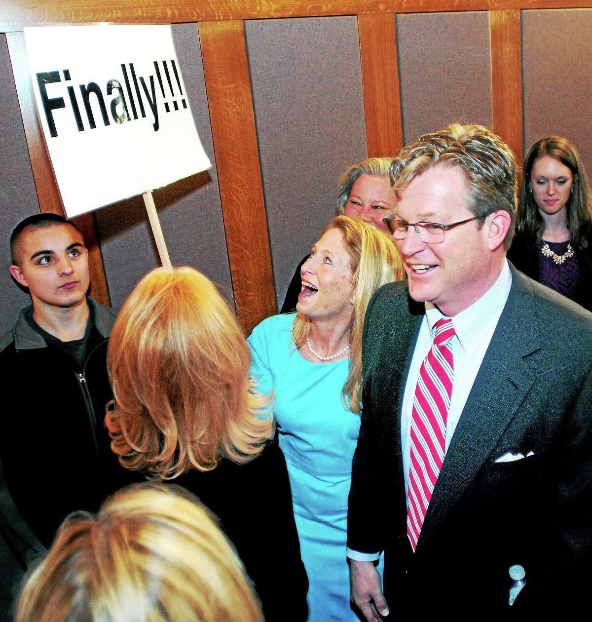 """Ted Kennedy Jr., right, and his wife, Kiki, center, share a laugh with their neighbor who made a """"Finally!!!"""" sign for his announcement to run for a state Senate seat at the Blackstone Memorial Library in Branford in April."""