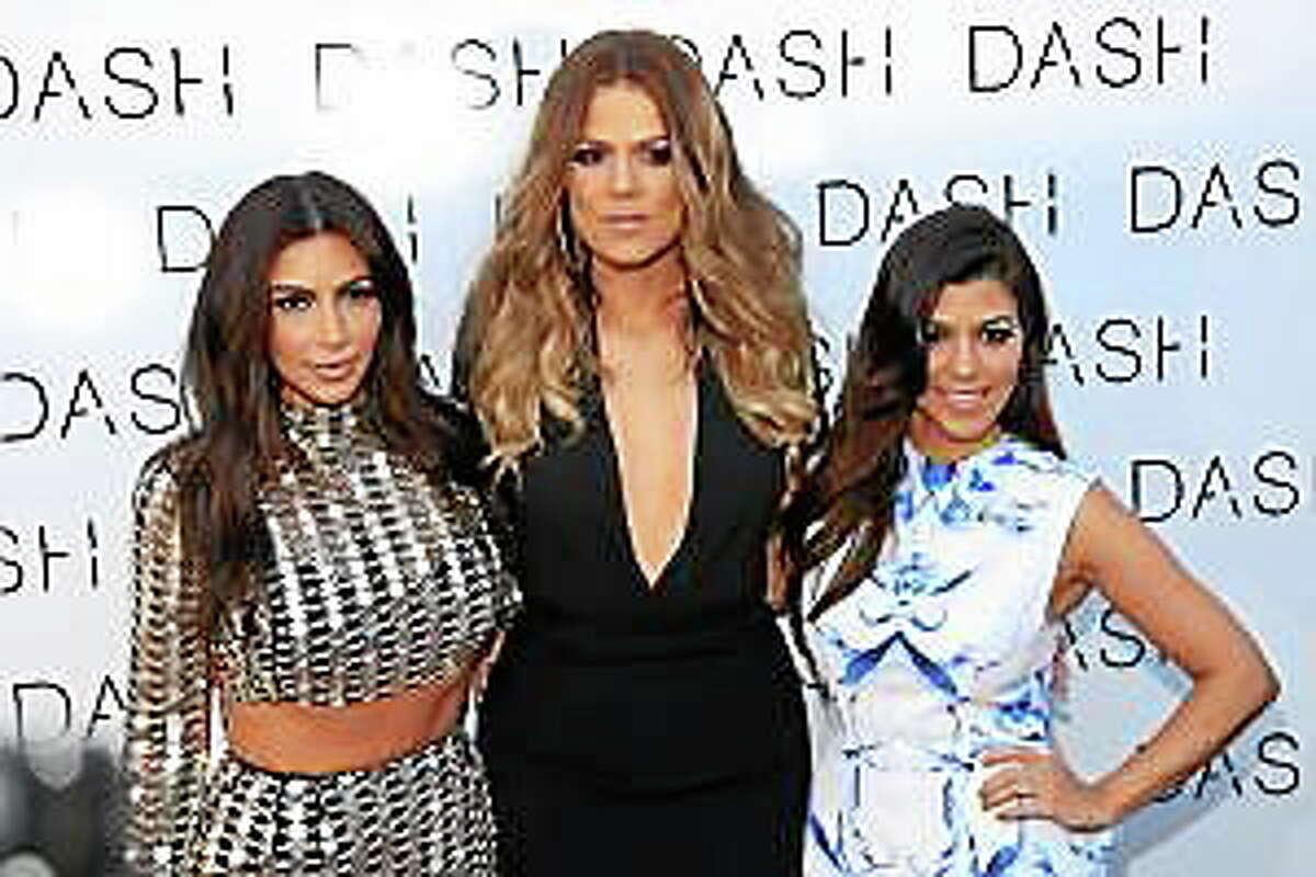 From left, Kim Kardashian, Khloe Kardashian and Kourtney Kardashian attend The Kardashian Family Celebrates the Grand Opening of DASH Miami Beach on Wednesday, March 12, 2014, in Miami Beach, Fla.