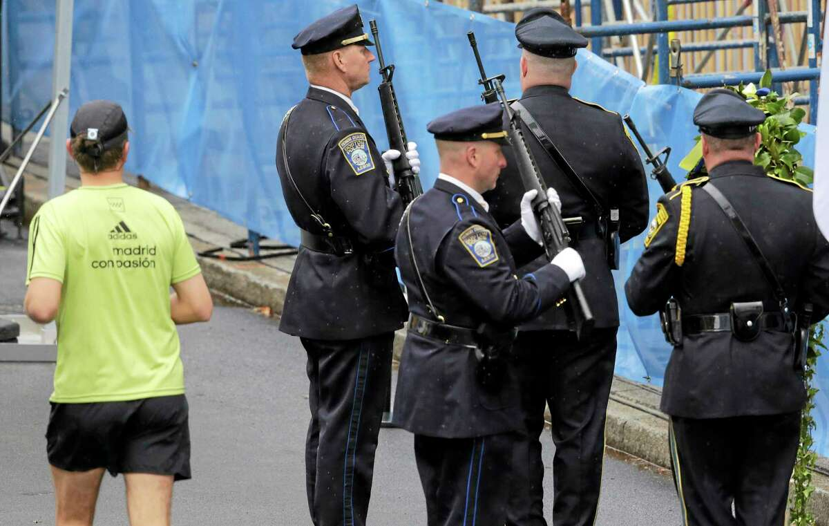 A runner passes as Boston Police honors change their post outside the Marathon Sports store, the site of the first of two bombs that exploded near the finish line of the 2013 Boston Marathon, Tuesday, April 15, 2014 in Boston. Three were killed and more than 260 injured in last year's explosions near the finish line of the race.