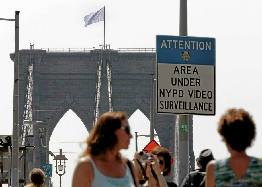 A white flag flies atop the west tower of New York's Brooklyn Bridge, Tuesday, July 22, 2014. Two large American flags atop the Brooklyn Bridge were replaced sometime during the night with white banners. Police crime scene and intelligence detectives were investigating how the flags were switched out on the famed span that connects Brooklyn and Manhattan, and there were no reports of suspicious activity, police said. (AP Photo/Richard Drew) Photo: AP / AP