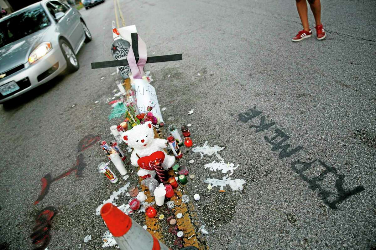 A makeshift memorial sits in the middle of the street where 18-year-old Michael Brown was shot and killed by police Monday, Aug. 11, 2014, in Ferguson, Mo. The FBI has opened an investigation into the fatal shooting of an unarmed black teenager on Saturday whose death stirred unrest in a St. Louis suburb. (AP Photo/Jeff Roberson)