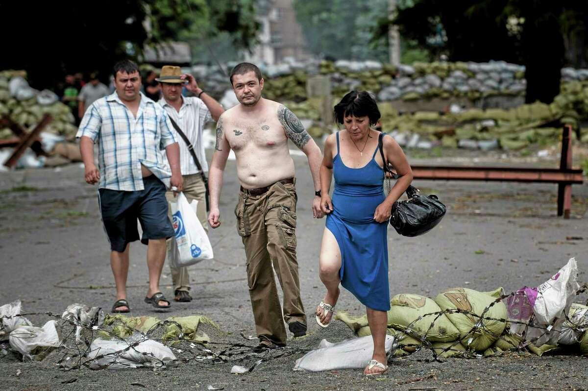 Local citizens walk through destroyed barricades drawn up between Ukrainian troops and pro-Russian fighters in Mariupol, eastern Ukraine, Friday, June 13, 2014. Ukraineís interior minister says that government troops have attacked pro-Russian separatists in the southern port of Mariupol. Arsen Avakov said Friday that four government troops were wounded as forces retook buildings occupied by the rebels in the center of the town. (AP Photo/Evgeniy Maloletka)