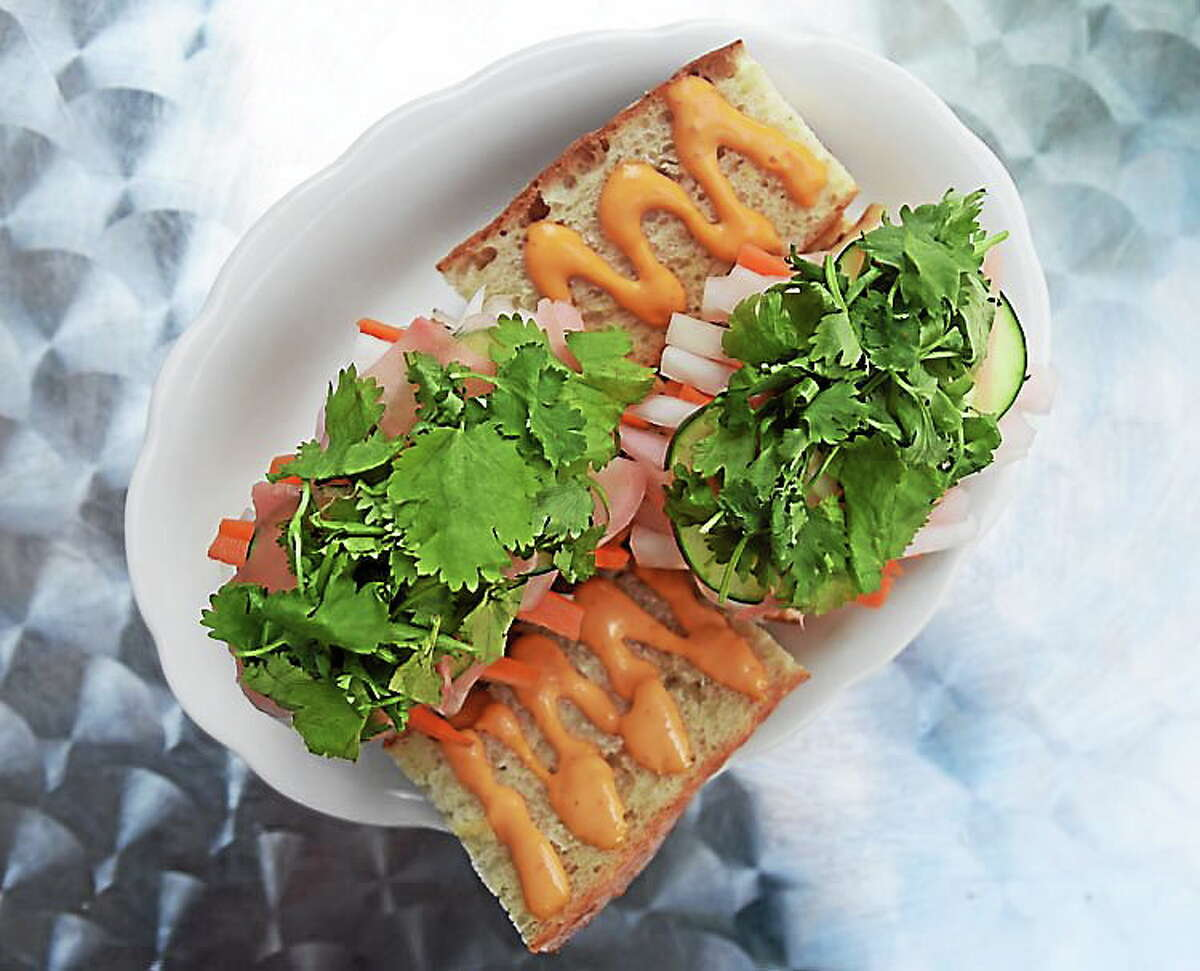 (Mara Lavitt — New Haven Register) The banh mi: grilled, marinated pork belly on one, tofu on the other, served on a baguette with chili sauce, pickled daikon, carrot, ginger, radish, white onion, cucumber and cilantro. Three Sheets.