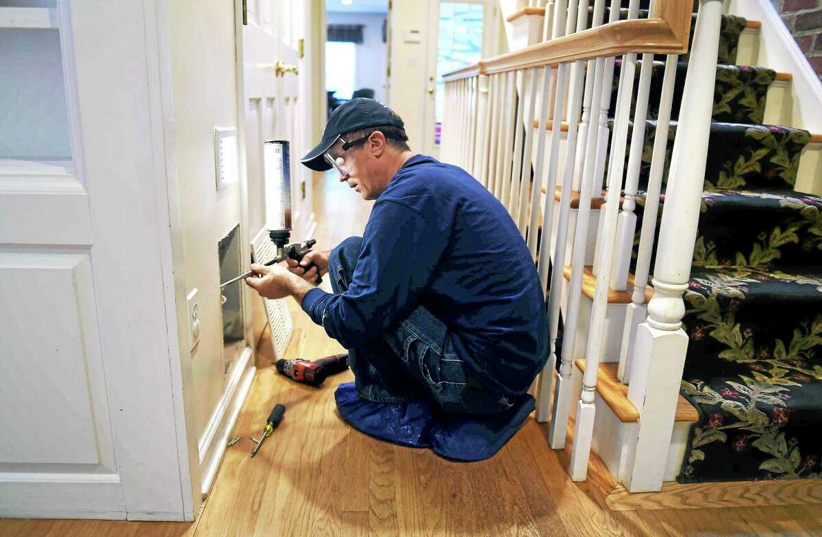 Vitalie Siretanu, energy efficiency specialist with New England Smart Energy, injects foam to seal around the edge of a vent during an energy audit at the home of DEEP Commissioner Rob Klee in Woodbridge Tuesday.