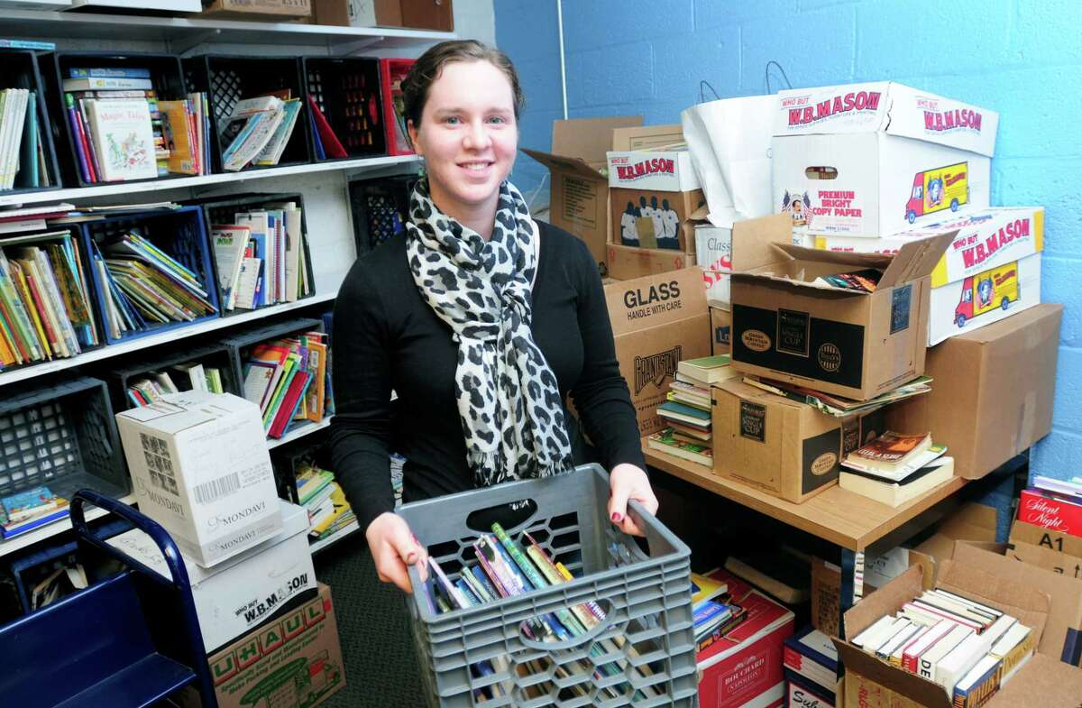 Amy Cobb is surrounded by books donated by Amity Middle School of Orange at New Haven Reads on 2/11/2014. Books from Amity Middle School of Bethany also were donated.