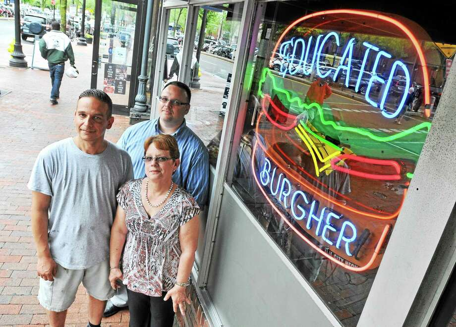 Kosta Vastakis, left, with his mother, Joanne, and brother, Jimmy, in front of their restaurant, the Educated Burgher, on Broadway in New Haven. Photo: Arnold Gold — New Haven Register