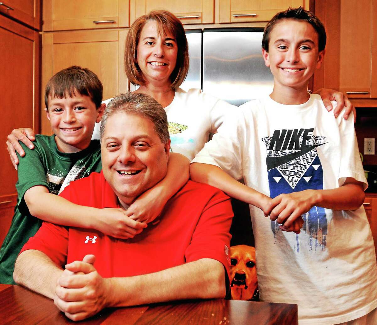Manuel Silva, his wife, Kris, and sons Daniel, 11, and Jason, 14, with their dog Fenway at their home.