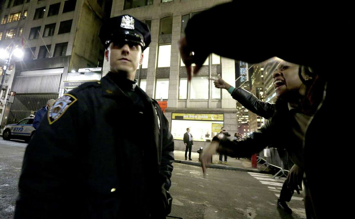 A woman, right, yells at a New York City Police officer during a protest after it was announced that the police officer involved in the death of Eric Garner is not being indicted, Wednesday, Dec. 3, 2014, in New York.
