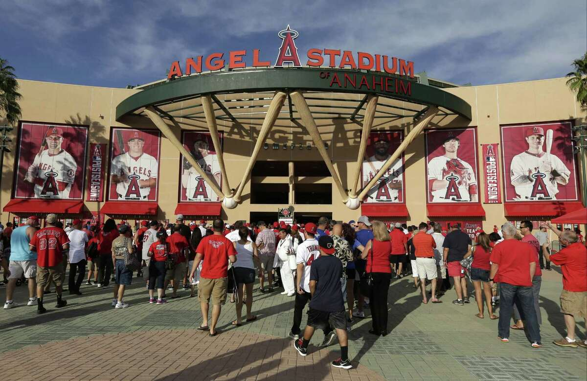 FILE - In this Oct. 3, 2014, file photo, fans enter Angel Stadium of Anaheim before Game 2 of baseball's AL Division Series between the Los Angeles Angels and the Kansas City Royals in Anaheim, Calif. In Southern California, police are looking Monday, Oct,. 6 for three men suspected of brutally beating a man in the Angels Stadium parking lot after the Angels' playoff night game on Friday, Oct. 3.