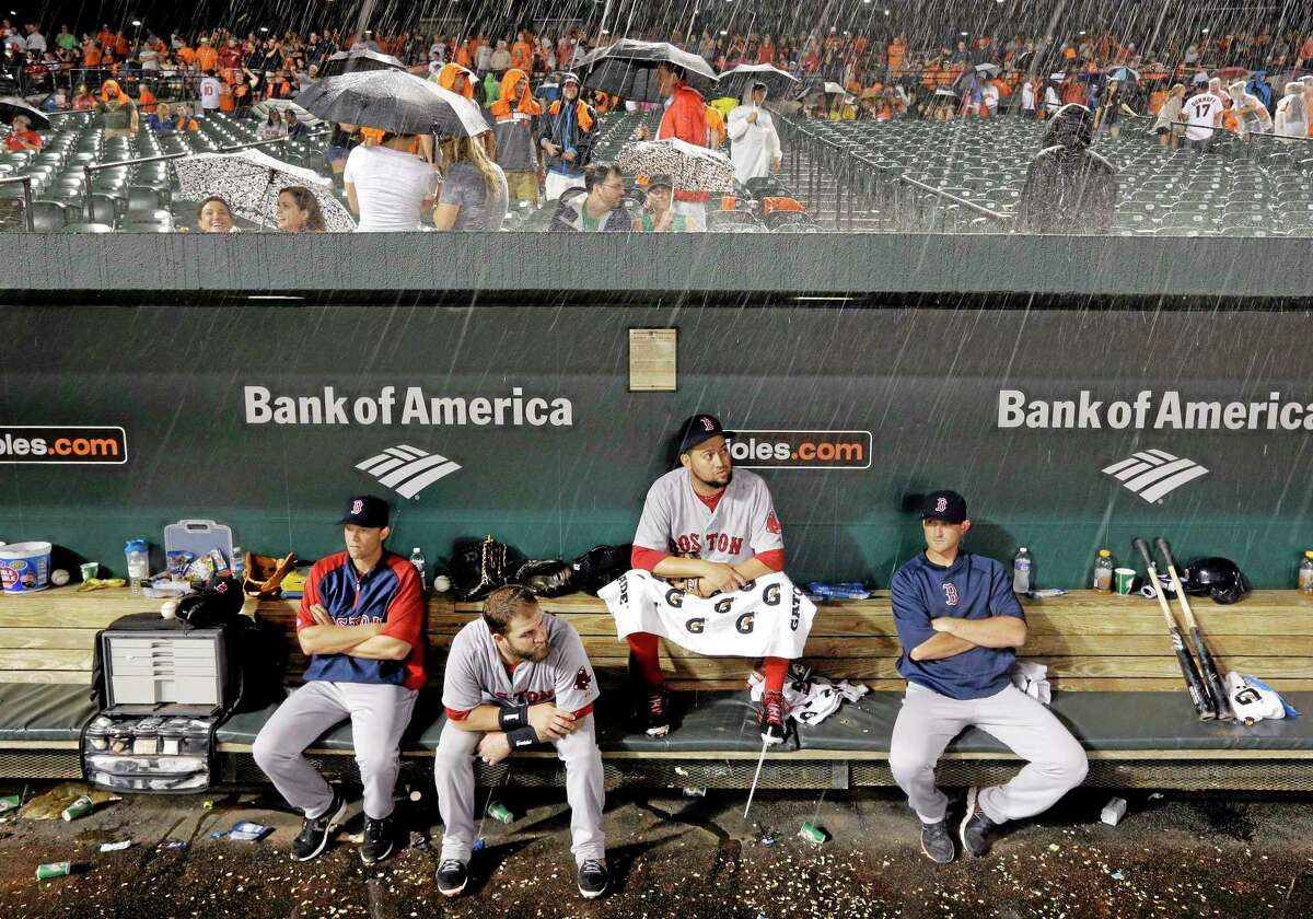Members of the Boston Red Sox sit in the dugout during a rain delay in a baseball game against the Baltimore Orioles on Wednesday.