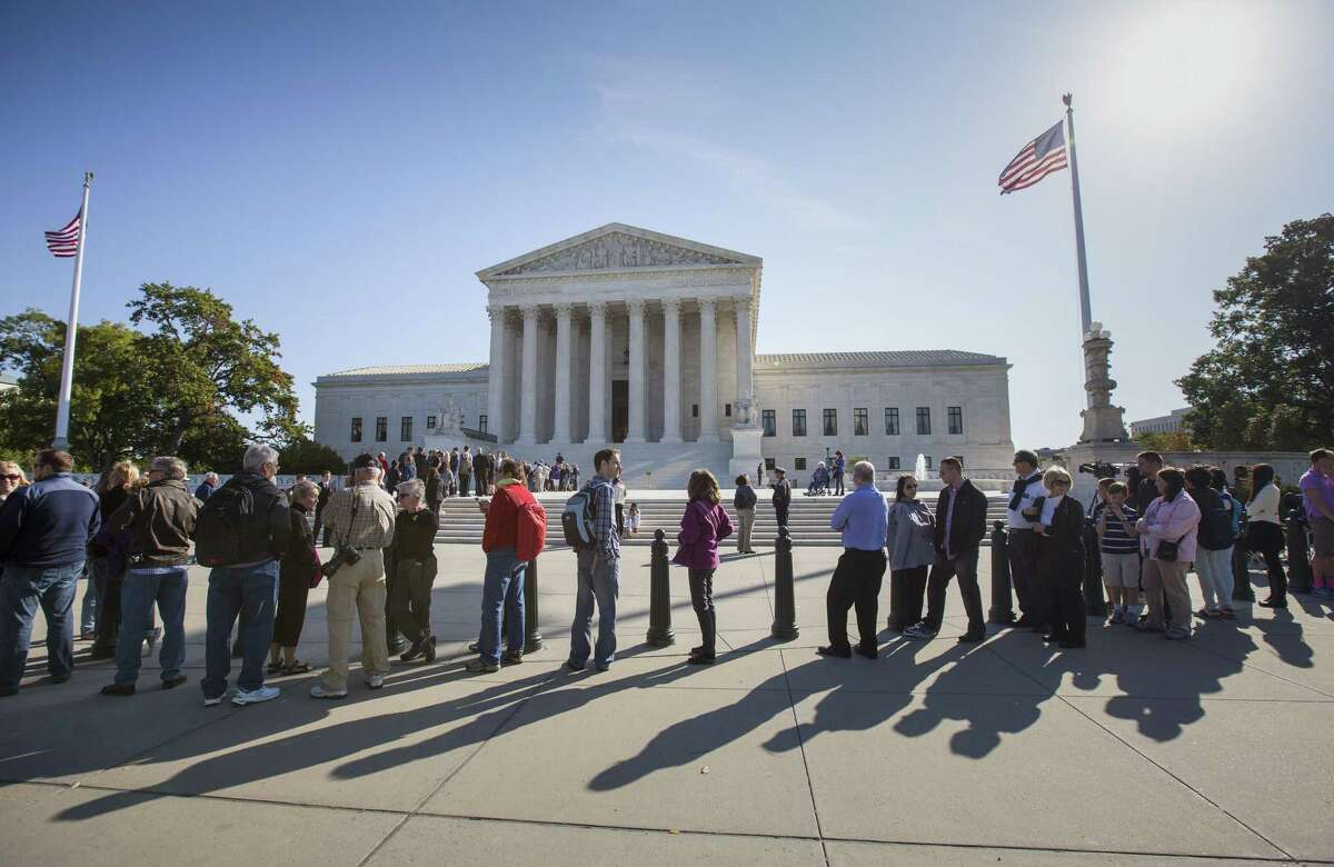 People wait to enter the Supreme Court in Washington, Monday, Oct. 6, 2014, as it begins its new term.