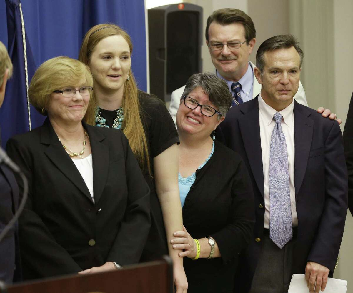 FILE - In this Tuesday May 13, 2014 file photo, plantiff's in the federal suit over Virginia's ban on gay marriage, Mary Townley, left, Emily Schall-Townley, second from left, Carol Schall, center, Tony London, second from right, and Tim Bostic, right, react to comments during a news conference after a hearing on Virginia's same sex-marriage ban in Richmond, Va.