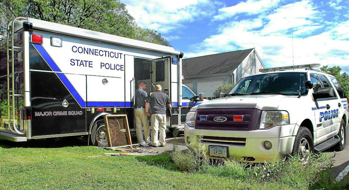 East Hampton Police Sgt. Timothy Dowty, right, talks with a member of the State Police Major Crime Squad at the Glastonbury Police Department parking lot following the discovery of the remains of a missing East Hampton woman in September 2012.