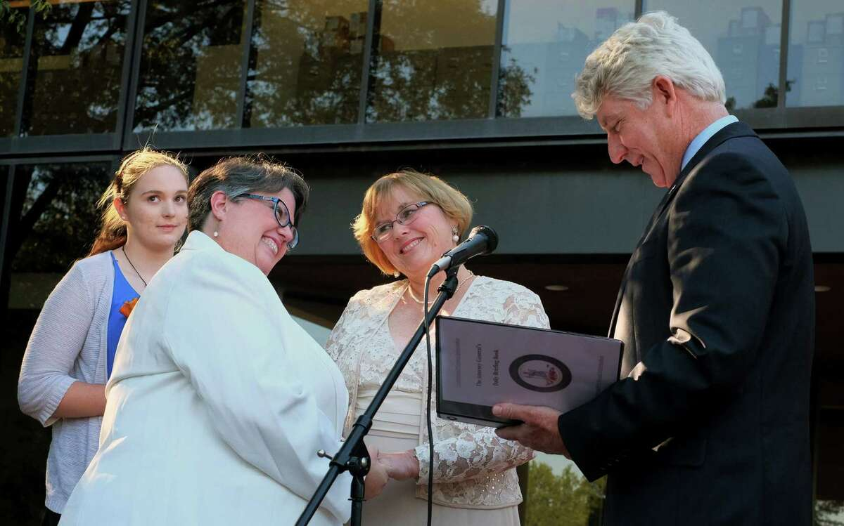 Virginia Attorney General Mark Herring, right, leads a renewal of vows for former plaintiffs Mary Townley, second from left, and her partner Carol Schall, second from right, outside the John Marshall Courts Building in Richmond, Va. Monday, Oct. 6, 2014. The Richmond area couple challenged Virginia's marriage ban.