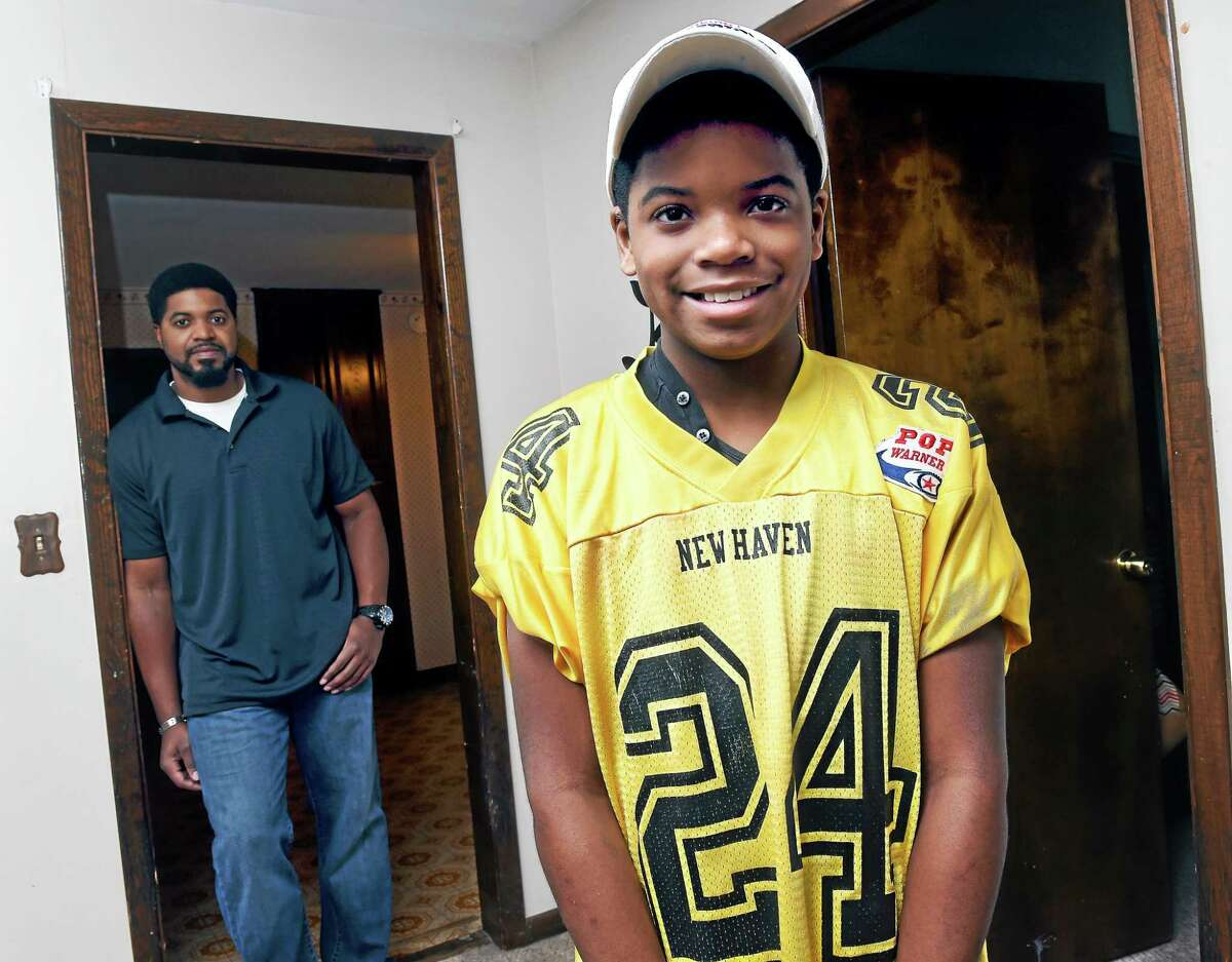 Robert Gathers (left) is photographed with his son, Keon, 12, at his home in Hamden on 12/2/2014.