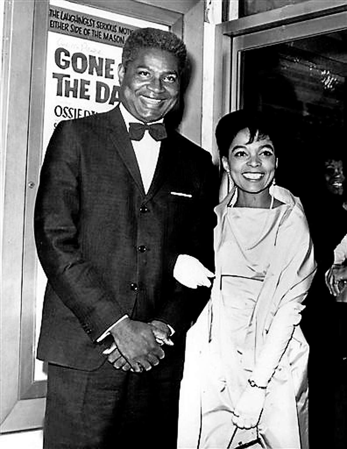 """In this Sept. 23, 1963, file photo, actors Ossie Davis, left, and Ruby Dee pose in front of the movie poster at the opening night gala of their film """"Gone Are the Days!"""" based on Davis' play """"Purlie Victorious,"""" at the Trans-Lux East Theater in New York City. Dee, an acclaimed actor and civil rights activist whose versatile career spanned stage, radio television and film, has died at age 91, according to her daughter. Nora Davis Day told The Associated Press on Thursday, June 11, 2014, that her mother died at home at New Rochelle, New York, on Wednesday night."""