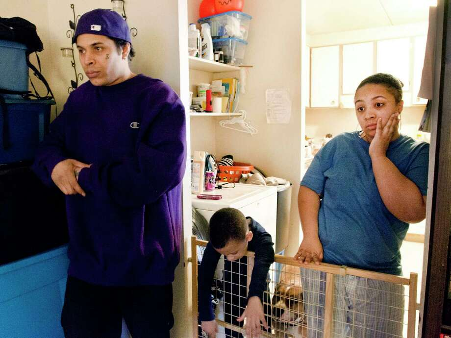 (Melanie Stengel-Register)   Left to Right: Jonathan Cruz, 34; Christian Garcia, 6; Ariel Garcia, 24, in Irene Santana's (not pictured) Church Street apartment Friday. Photo: Journal Register Co.