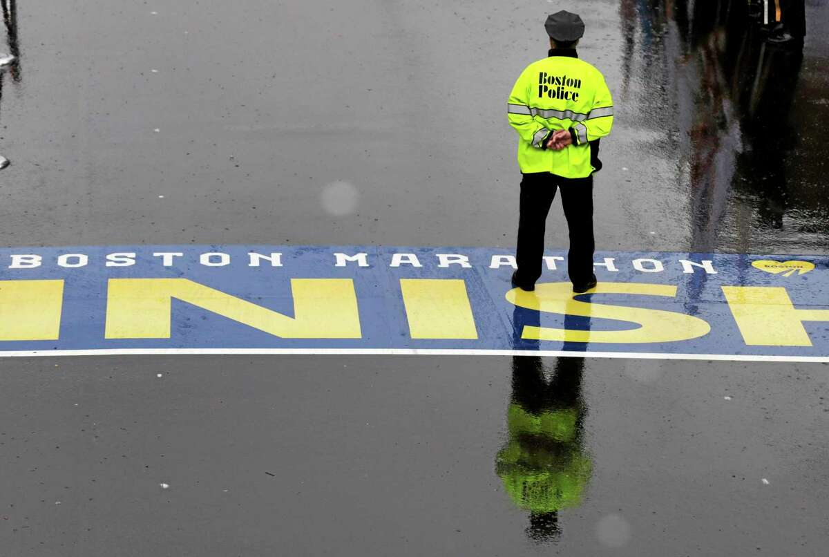 A Boston police officer pauses on the finish line during a tribute in honor of the one year anniversary of the Boston Marathon bombings, Tuesday, April 15, 2014 in Boston. (AP Photo/Charles Krupa)