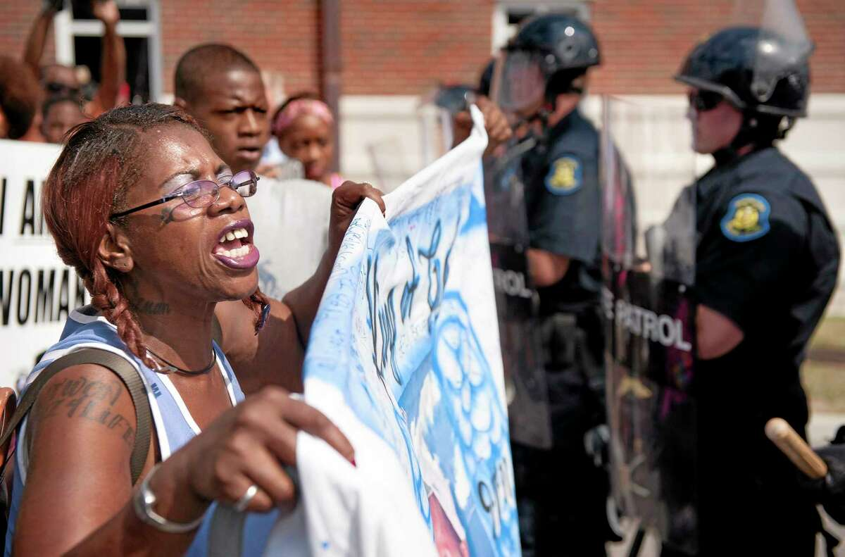 Marcelle Stewart, left, confronts police officers during a march and rally in downtown Ferguson, Mo., Monday, Aug. 11, 2014.