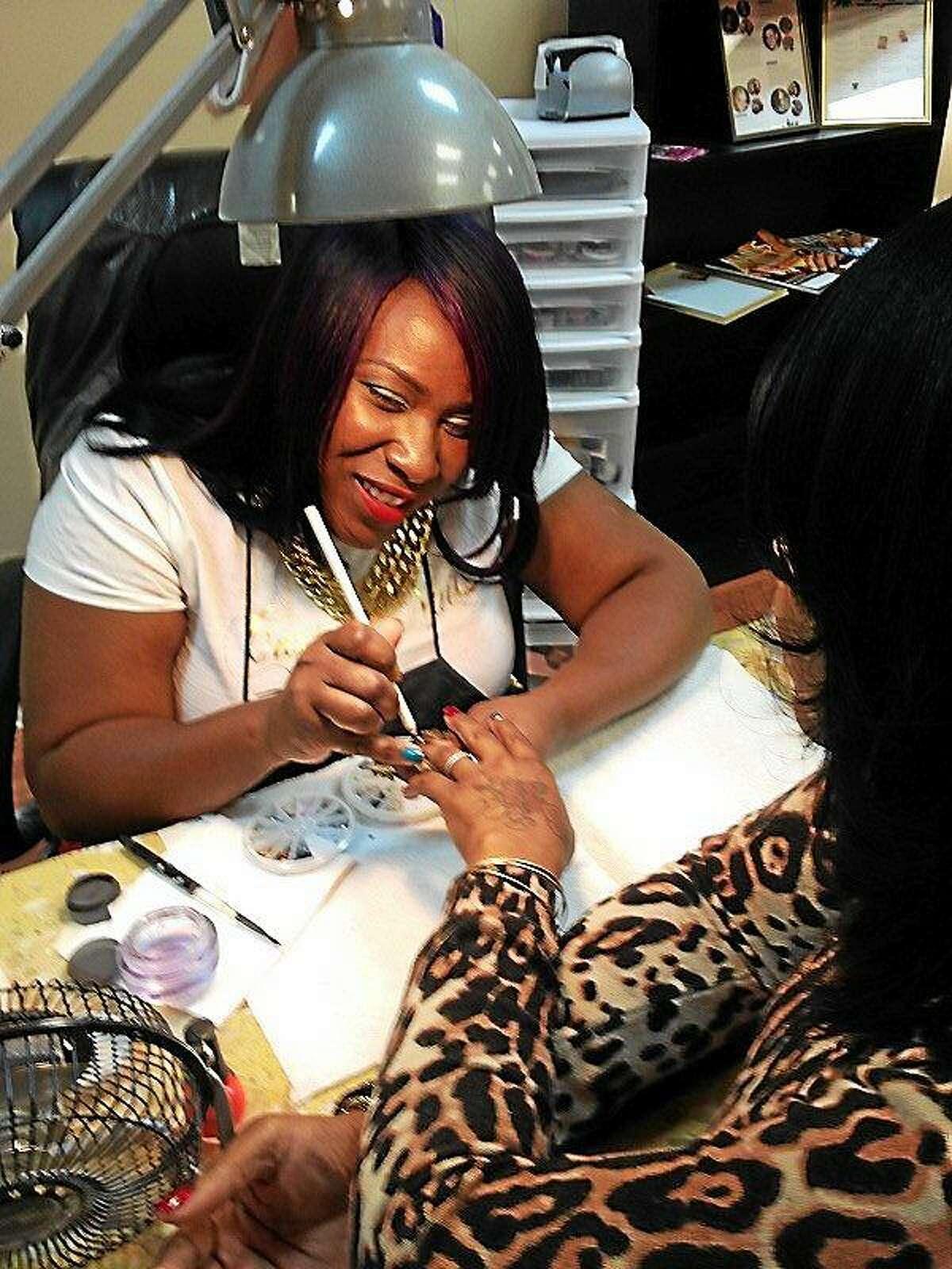 Nail stylist Temeka Jackson works on a unique nail design for regular customer Keisha Edwards.