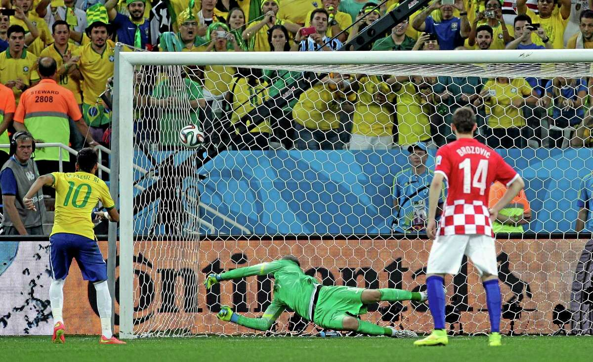 Brazil's Neymar, left, scores his second goal during the group A World Cup soccer match between Brazil and Croatia on Thursday.