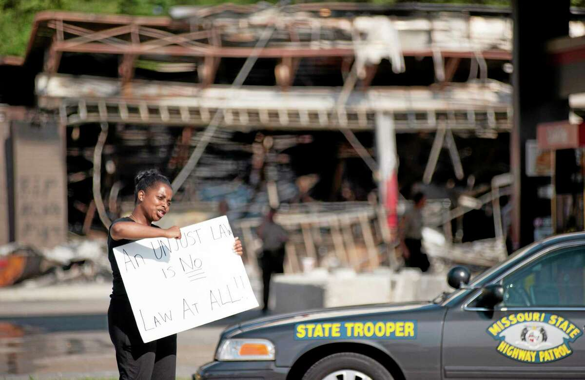 Protesters appeal to motorists for support while rallying on Monday, Aug. 11, 2014 in front of the QT gas station in Ferguson, Mo. that was looted and burned during rioting overnight that followed a candlelight vigil honoring 18-year-old Michael Brown, who was shot Aug. 9, 2014 by Ferguson police officers.